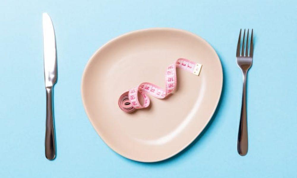 plato-redondo-cinta-metrica-dentro-tenedor-cuchillo-sobre-fondo-azul_79075-4865